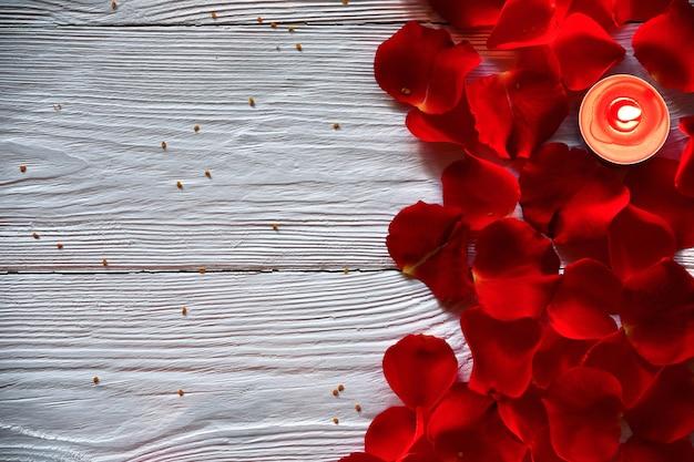 Pétalas de rosa vermelhas e vela acesa vermelha em um branco de madeira. vista do topo. conceito dia dos namorados