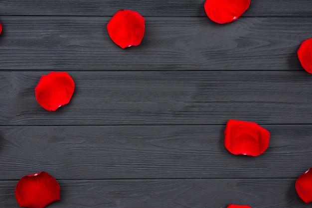 Pétalas de rosa vermelhas na superfície de madeira