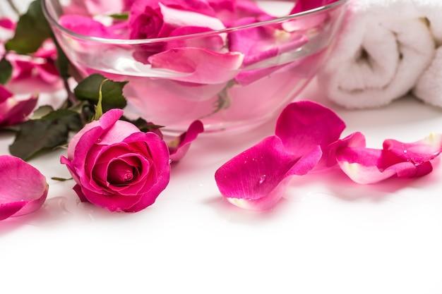 Pétalas de rosas em uma tigela com toalhas e água pura sobre o branco ... conceito de spa e bem-estar.