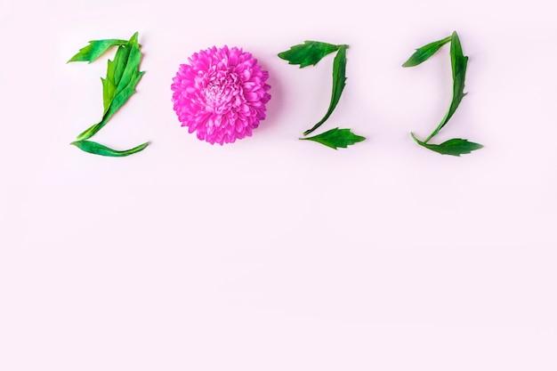 Pétalas florais e folhas em forma de números 2022. inscrição no fundo rosa. conceito de ano novo.