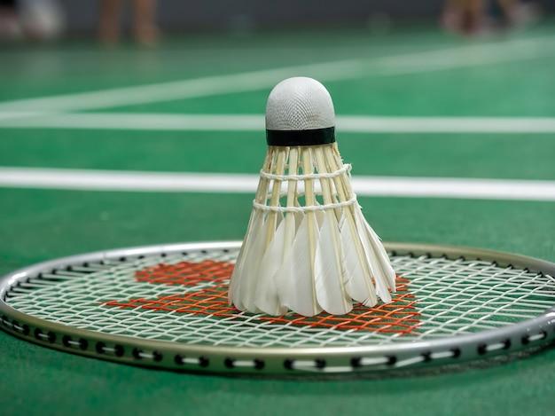 Peteca branca e raquete do badminton em uma corte verde.