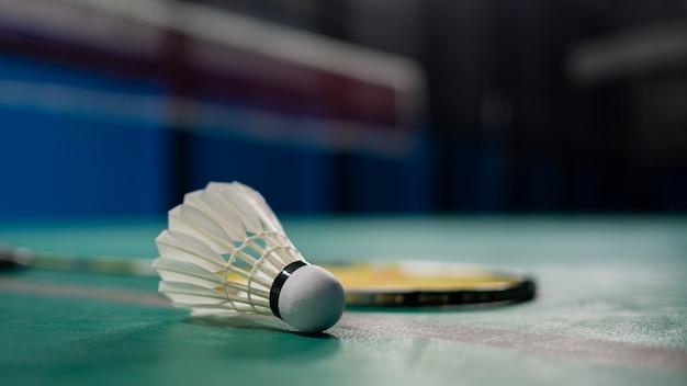 Peteca de badminton com raquete em piso verde
