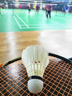 Peteca do badminton do conceito do esporte na raquete com fundo borrado da corte de badminton