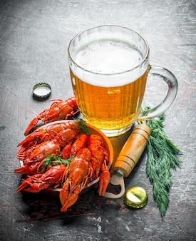 Petisco de cerveja. lagostins cozidos com cerveja e endro. em fundo escuro rústico