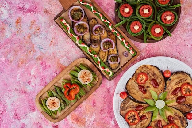 Petisco de vegetais e salada em tábuas de madeira.