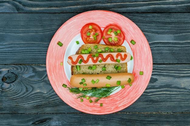 Petisco e vegetais do sanduíche da salsicha no pão inteiro da grão.
