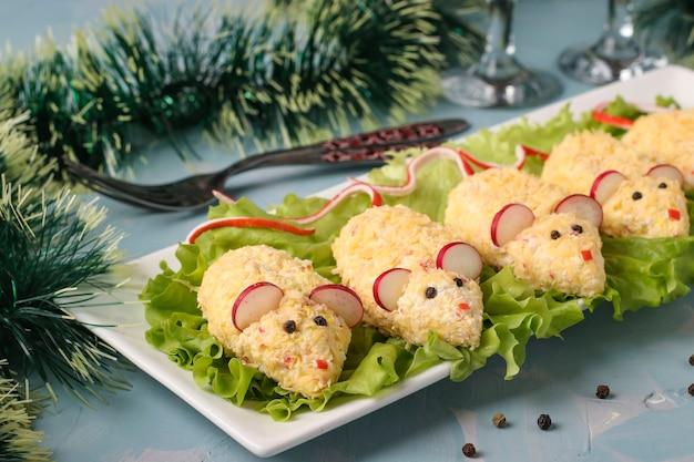 Petisco festivo ratos de queijo, ovos e palitos de caranguejo em fundo azul claro, comida simbólica para o ano novo, closeup, orientação horizontal