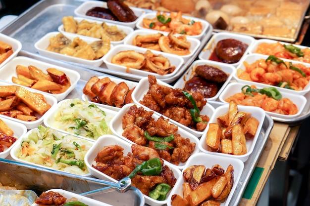 Petisco japonês do close up e da variedade da colheita e alimentos fritados, venda no mercado de rua de kuromon. é tão delicioso e muito barato.