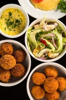 Petiscos brasileiros mistos, incluindo doces, frango frito, saladas, sopas, batatas fritas e quibe
