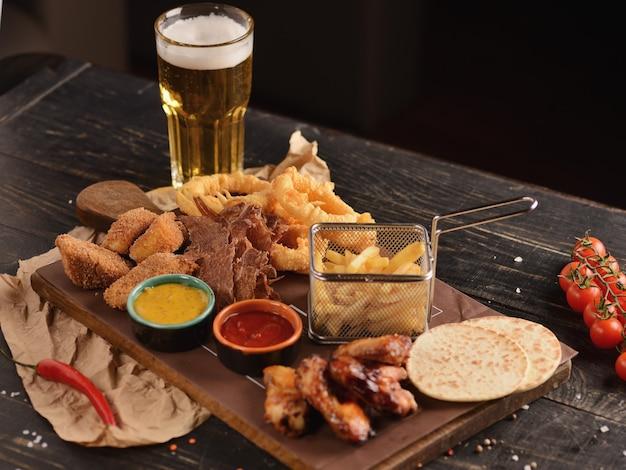 Petiscos de cerveja. asas de frango frito, batata frita, rodelas de cebola, queijo em massa e carne seca. em uma placa de madeira