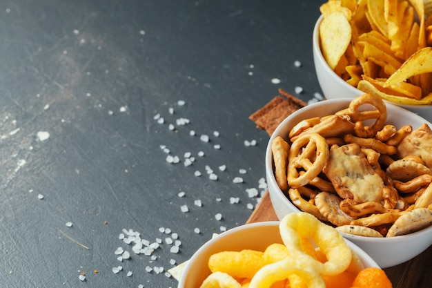 Petiscos de cerveja na mesa de pedra. vários biscoitos, batatas fritas. vista do topo