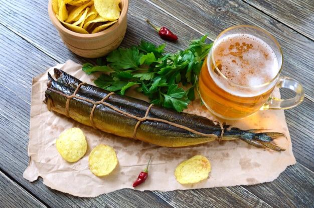 Petiscos de cerveja. peixe defumado, batatas fritas, um copo de cerveja em uma mesa de madeira.