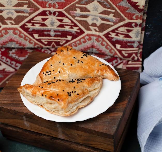 Petiscos de massa folhada em um prato branco sobre uma tábua de madeira