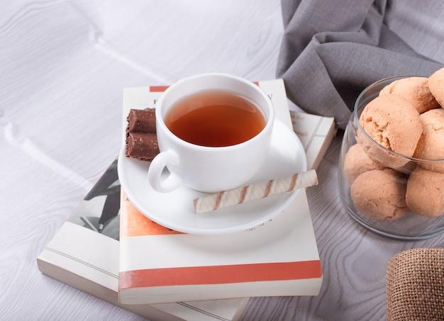 Petiscos doces, xícara de chá e chocolate e livro