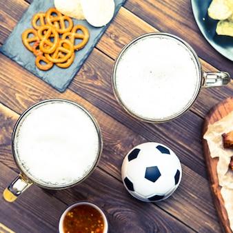 Petiscos e cervejas na mesa para a festa de futebol e assistir a partida de futebol.