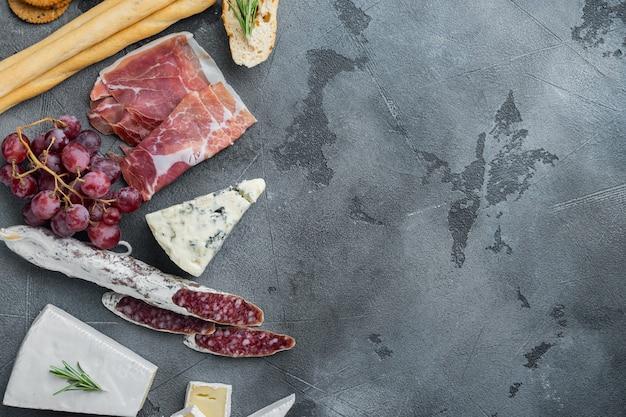 Petiscos italianos, queijo de carne, conjunto de ervas, em fundo cinza, plano com espaço de cópia