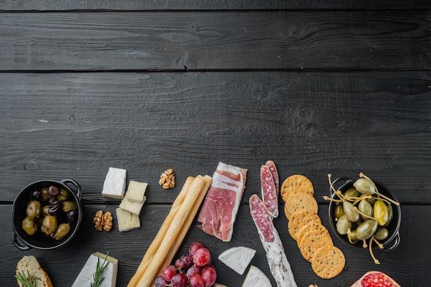 Petiscos italianos, queijo de carne, conjunto de ervas, mesa de madeira preta, vista de cima