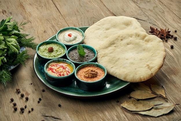 Petiscos orientais clássicos com pita - meze. situado em uma tigela pequena - hummus, pasta de pimenta, muitas vezes com nozes, iogurte, pasta de berinjela.
