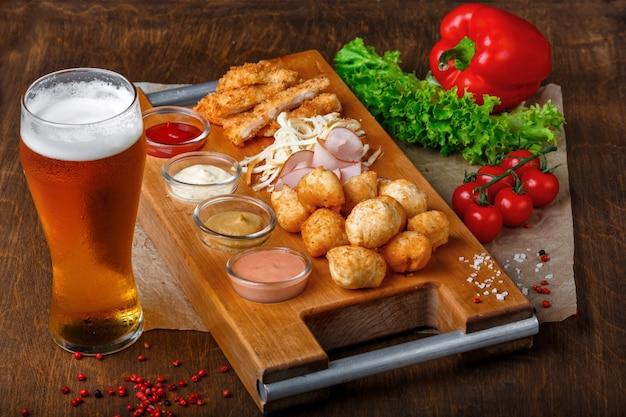 Petiscos para cerveja inclui bolas de queijo frito, queijo pigtail, presunto e caranguejo em uma tábua de madeira