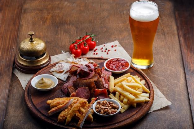 Petiscos para cerveja ou álcool e inclui carne de porco fumada, batatas fritas, pão frito, varas de caranguejo e nozes