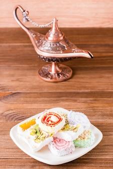 Petiscos turcos e lâmpada árabe em uma mesa de madeira.