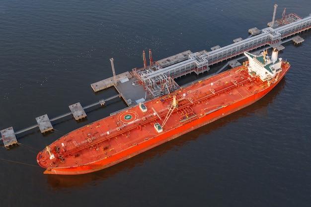 Petroleiro em porto industrial na descarga de conteúdo a granel, vista aérea.