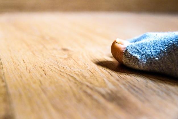 Peúga quebrada com um furo no dedo grande do homem, conceito da pobreza durante a crise.