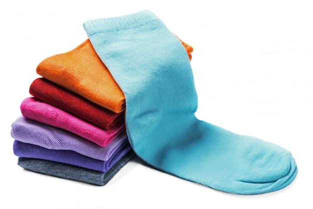 Peúgas coloridas de matéria têxtil isoladas em um branco