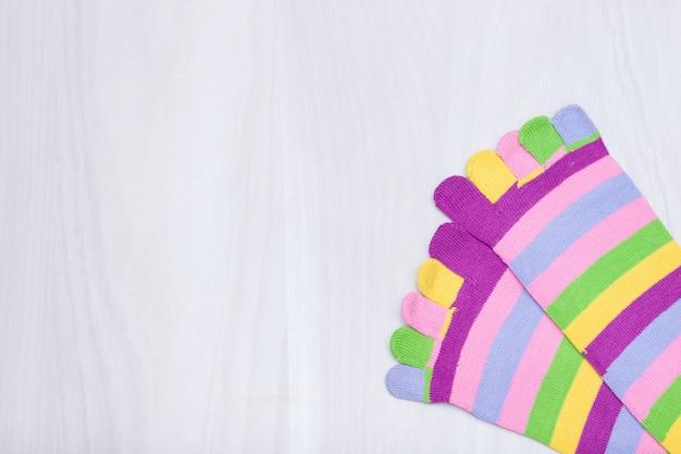 Peúgas listradas coloridas com os dedos no fundo de madeira branco. copie o espaço, plana leigos.