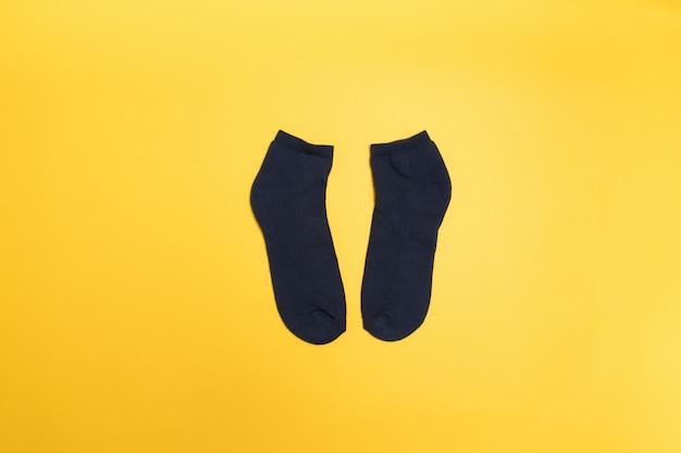Peúgas pretas em um fundo amarelo, vista superior.