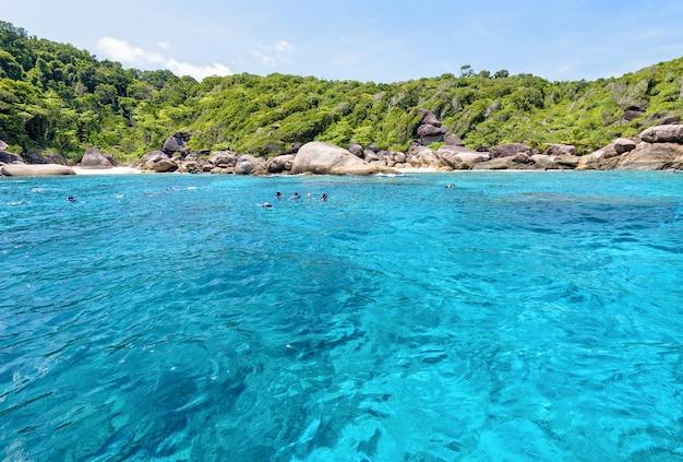 Phang nga, tailândia - 1º de maio de 2015: os turistas desfrutaram de mergulho com snorkel no mar azul sob o sol e o céu durante o verão na ilha ko ba ngu no parque nacional mu ko similan