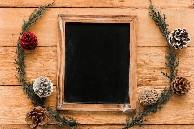 Photo frame perto de galhos de coníferas e senhos de ornamento