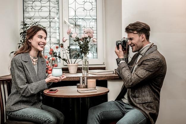 Photoshoot homem tirando foto de uma mulher sorridente segurando uma xícara de chocolate