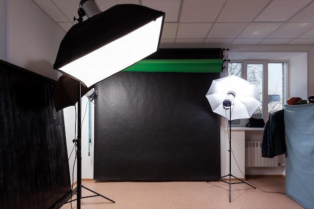 Photostudio com equipamento de estúdio: preto, croma verde para fotografia, flashes de estúdio, defletores, octoboxes