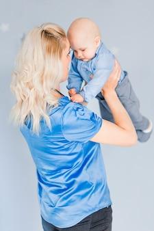 Phto da mãe brinca e joga uma criança no quarto das crianças contra o fundo da parede azul
