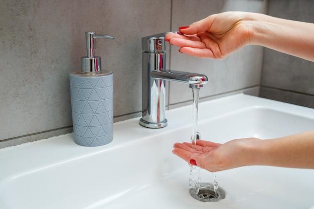 Pia branca com torneira prateada no banheiro. lata cinza com sabonete líquido para as mãos. ligar a água da torneira, higiene pessoal das mãos. lavar as mãos em água corrente