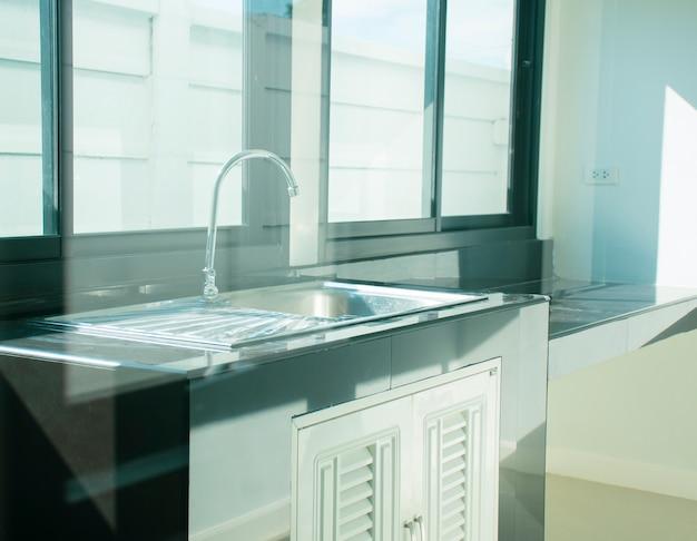 Pia de aço inoxidável com torneira de água em uma sala de cozinha de uma casa.