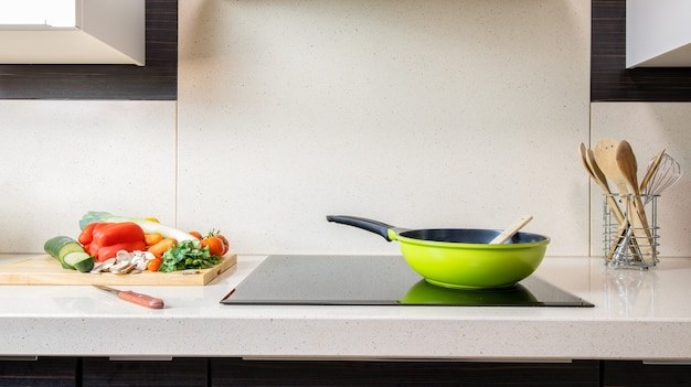 Pia de cozinha em mármore com vitrocerâmica - preparação de vegetais - cópia espaço.