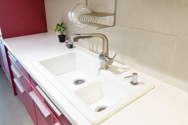Pia de cozinha inoxidável e água da torneira na cozinha. aparelhos incorporados. utensílio de cozinha