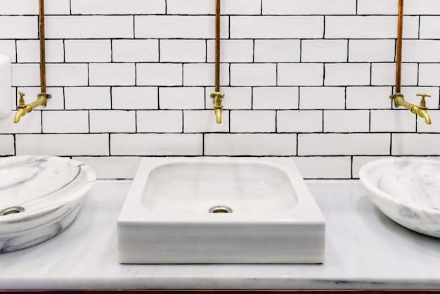 Pia de mármore em um banheiro público com torneira de água retro dourado com tubos de cobre na parede