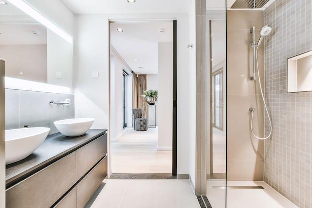 Pia e espelho localizados perto do chuveiro