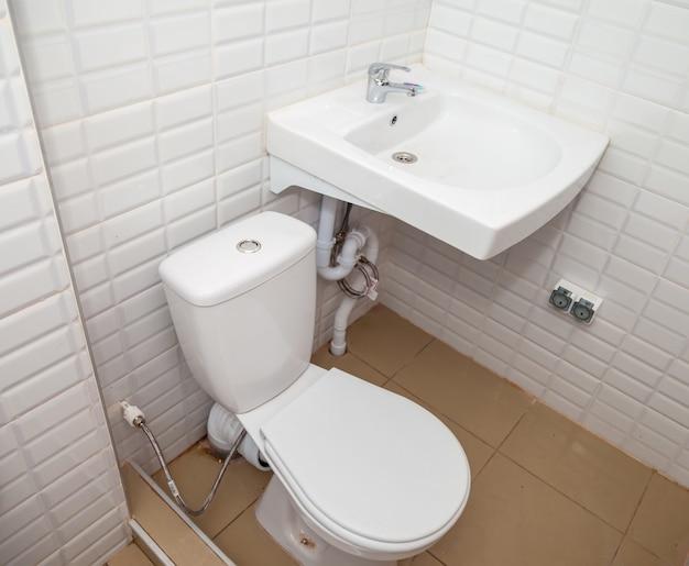 Pia e vaso sanitário brancos no banheiro contra a parede de azulejos claros