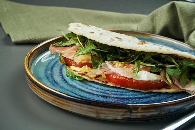 Piadina - clássico italiano tortilla-pão com presunto, rúcula, mussarela e tomate em um prato azul na mesa de madeira. sanduíche rápido. feche acima, foco seletivo