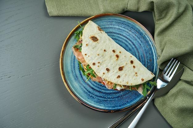 Piadina - clássico italiano tortilla-pão com presunto, rúcula, mussarela e tomate em um prato azul na mesa de madeira. sanduíche rápido. vista superior, plana leigos com espaço de cópia