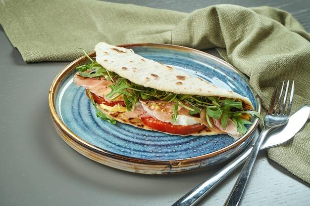 Piadina - clássico italiano tortilla-pão com presunto, rúcula, mussarela e tomate em um prato azul na mesa de madeira. sanduíche rápido