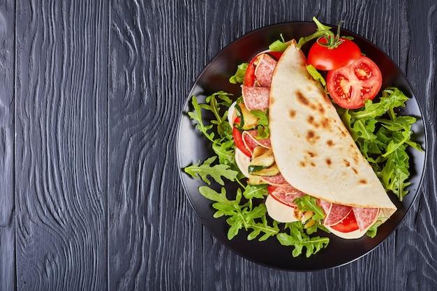 Piadina italiana com mussarela, tomate, fatias de salame, abobrinha grelhada e rúcula em um prato preto sobre uma mesa de madeira preta
