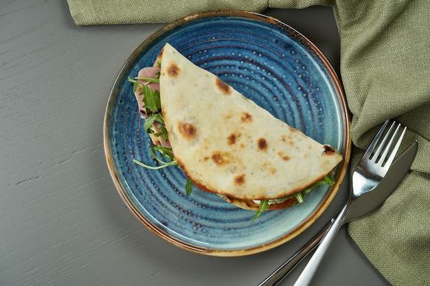 Piadina - pão de tortilla italiano clássico com vitela de vitelo, rúcula, mussarela e tomate em um prato azul na mesa de madeira. sanduíche rápido. vista superior, cópia espaço, plana leigos
