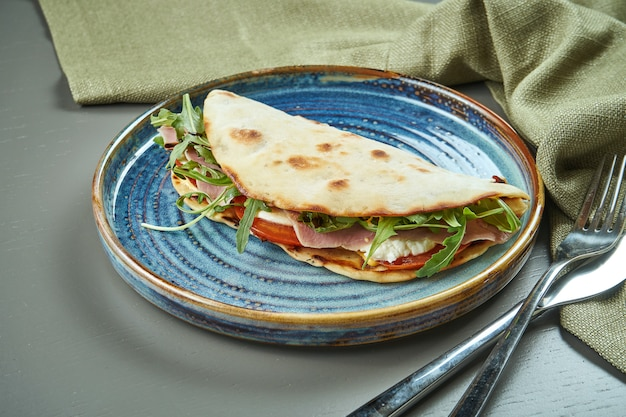 Piadina - pão de tortilla italiano clássico com vitela de vitelo, rúcula, mussarela e tomate em um prato azul na mesa de madeira. sanduíche rápido