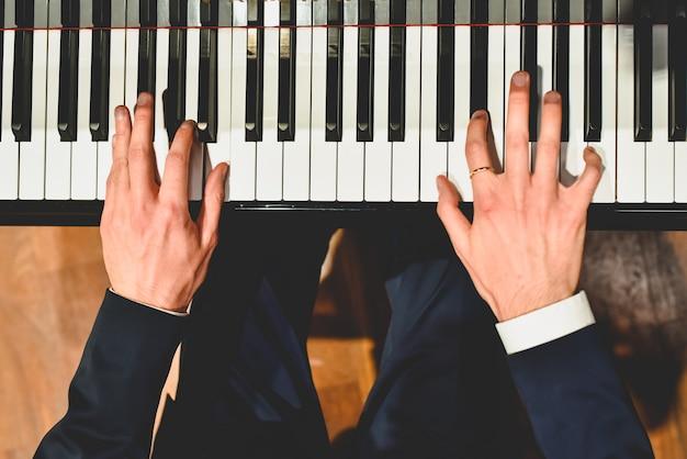 Pianista, executando uma peça em um piano de cauda com teclas brancas e pretas