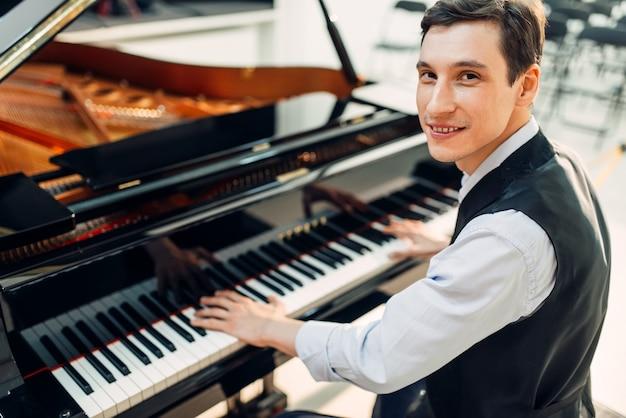 Pianista masculino posa ao piano de cauda preto